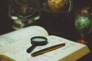A magnifying glass on an old book, research about the origins of open innovation